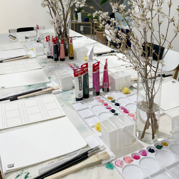 The workshop table is set with Sakura and art supplies